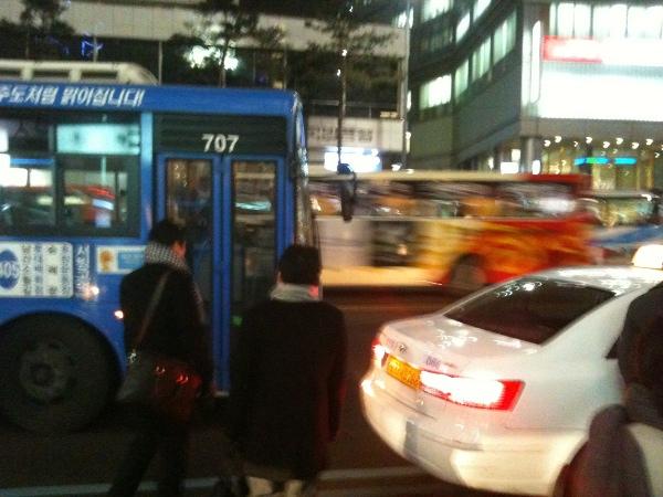 사람들은 차도를 하나 넘어 가야 버스를 탈 수있다.